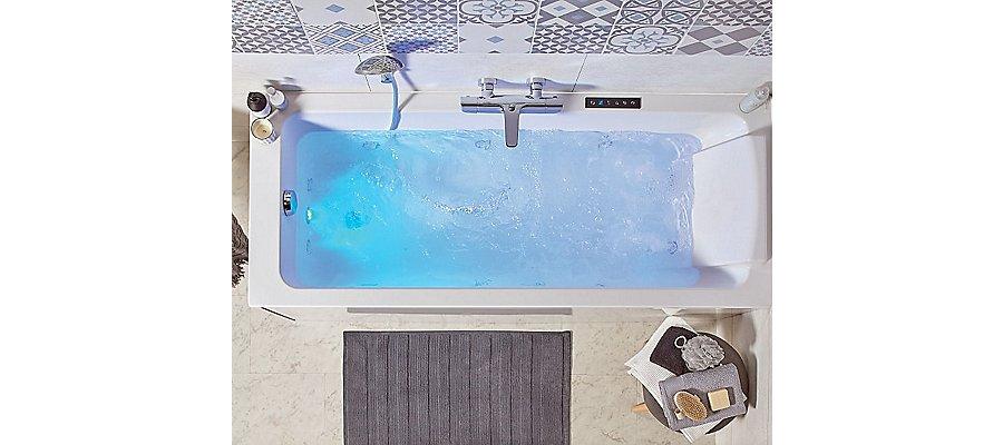 Du carrelage mural à motifs bleus et blancs pour embellir une salle de bains contenant une baignoire BALNÉO