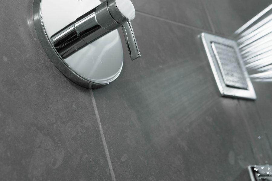 Du carrelage sombre sur les murs d'une salle de bains qui contraste avec la robinetterie en chrome