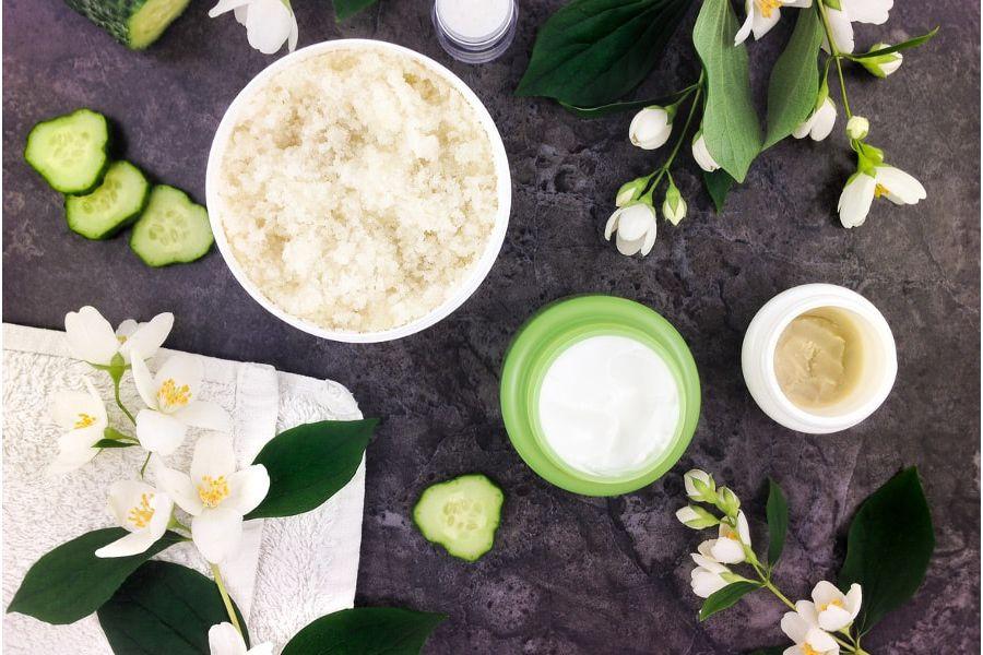Des crèmes et gommages naturels entourés de fleurs banches pour des soins dans la salle de bains