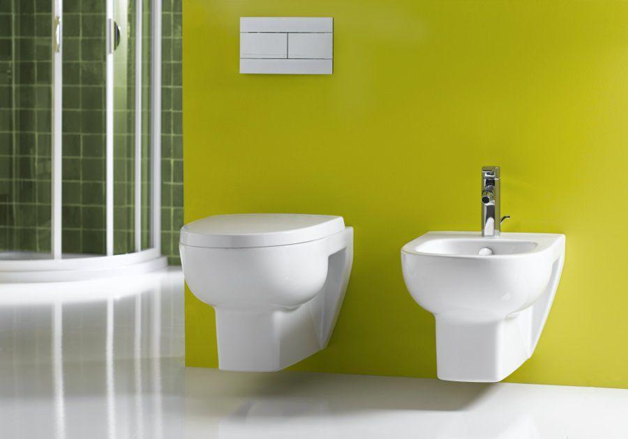 Des toilettes et un bidet aux murs de couleurs vertes claires