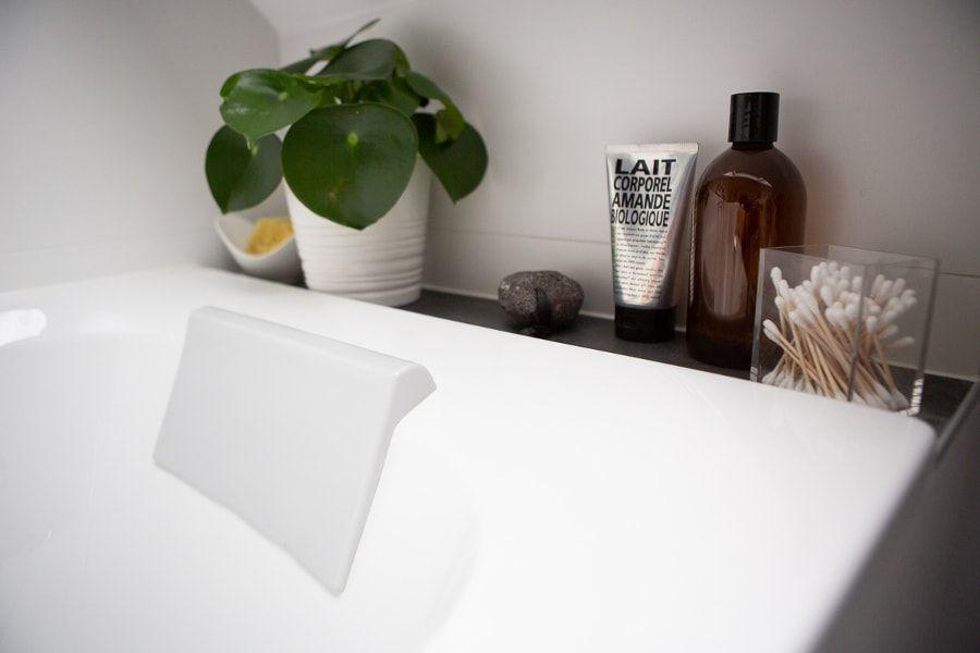 Une baignoire décorée d'un pot de plante verte dans le recoin de la salle de bains