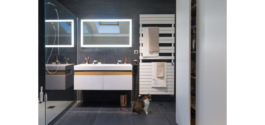 Une grande salle de bains avec un grand meuble vasque blanc un grand miroir et une poubelle couleur cuivrée