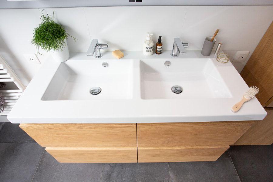 Une double vasque blanche avec un meuble sous plan-vasque en bois clair dans une salle de bains