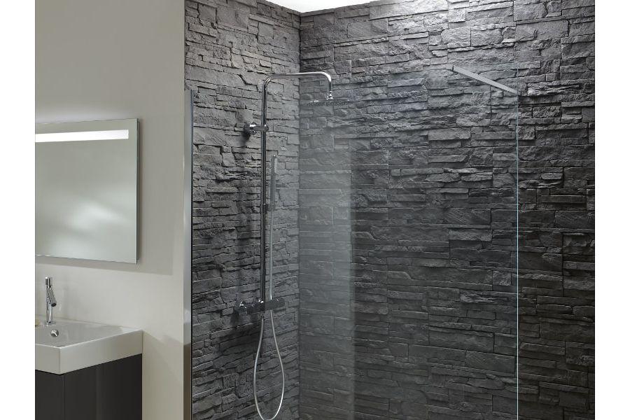 Une douche avec paroi fixe transparente et des murs revêtus de parements