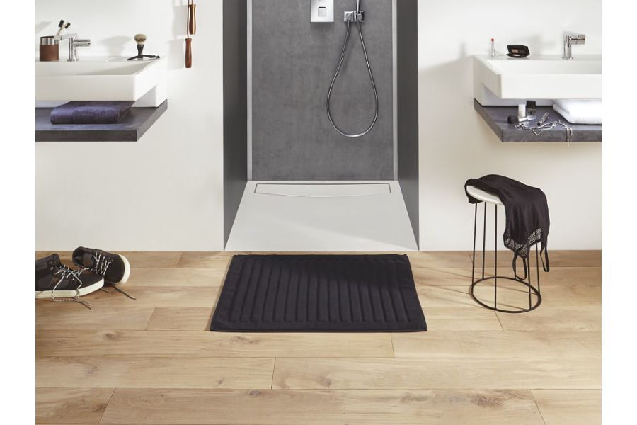 Du parquet clair dans une salle de bains tendance avec un tapis au sol et une douche encastrée