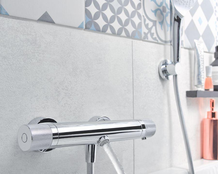 Du carrelage à motif bleu près de la robinetterie chromée d'une salle de bains