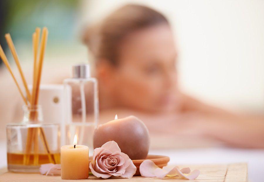 Une femme allongée qui se détend avec de l'encens et des bougies pour des odeurs apaisantes