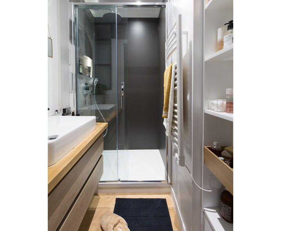 Une petite salle de bains en longueur avec de l'espace menant à la douche