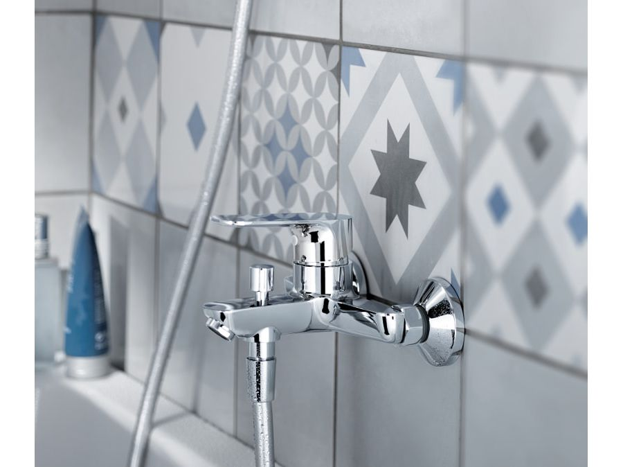 De la faïence en frise dans une salle de bains près d'une baignoire avec une robinetterie OSCAR
