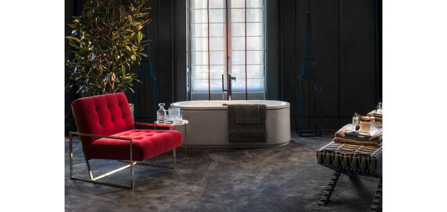 Un fauteuil rouge velours design dans une grande salle de bains chic