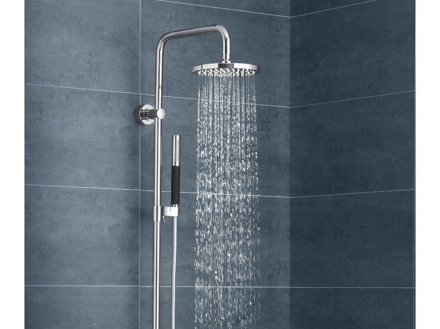 Un espace de douche avec de grands carrelages bleus foncés derrière une robinetterie TOOBI signée Jacob Delafon