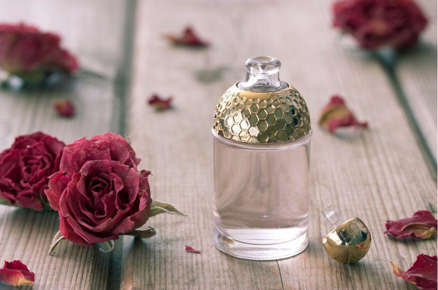Un flacon d'huile essentielle avec une rose rouge pour une ambiance comme dans un spa