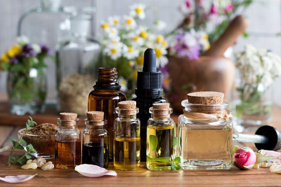 Une sélection d'huiles essentielles avec divers herbes et fleurs