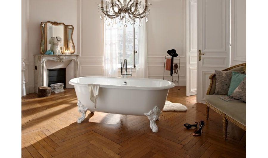 Une salle de bains parisienne au style haussmannien avec une grande baignoire d'époque blanche au milieu de la pièce, du parquet au sol, et un lustre à pampilles au plafond