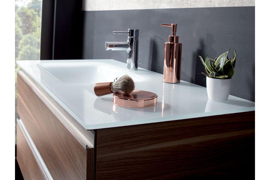 Un meuble vasque en bois avec un plan en laque brillante blanche et de la décoration