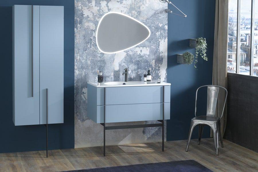 Une grande salle de bains avec des meubles bleus et un grand miroir asymétrique aux contours LED