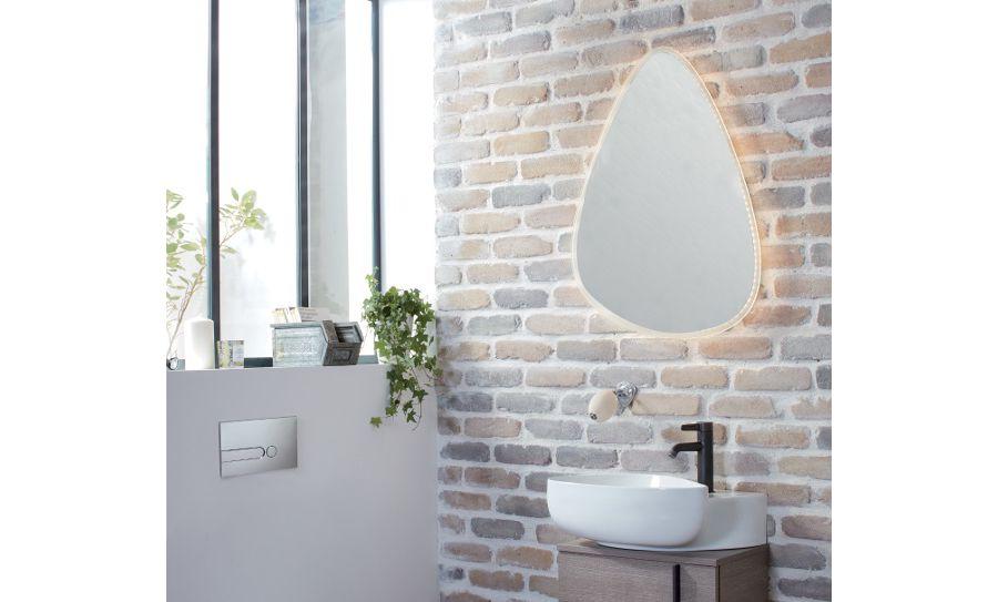 Un miroir asymétrique aux contours LED dorés dans une salle de bains décorée d'objets de décoration