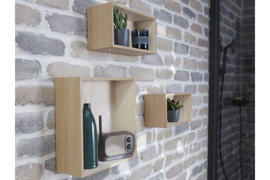 Des casiers de décoration en bois fixés à un mur en briques de pierres