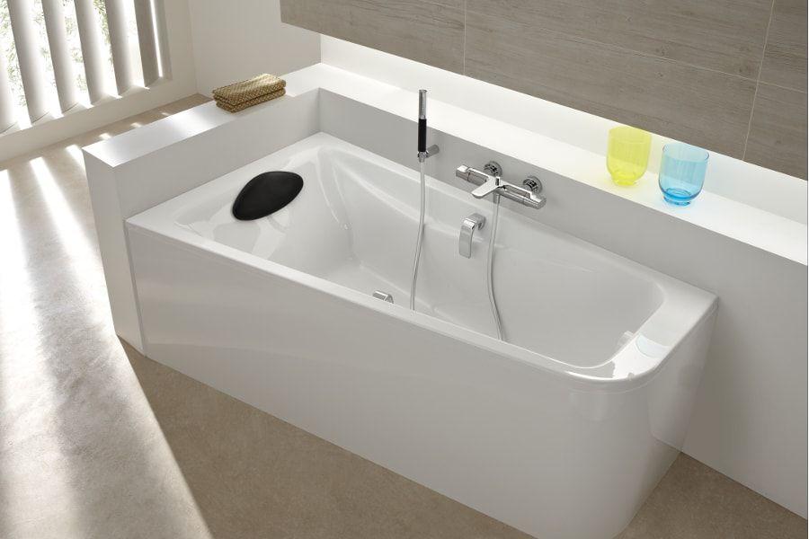 Une baignoire blanche asymétrique ODEON UP dans une salle de bains avec un repose-tête