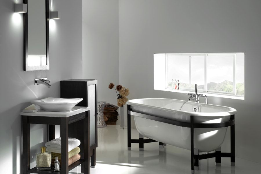 Une salle de bains épurée toute blanche avec une baignoire près de la fenêtre, un meuble vasque et une vasque