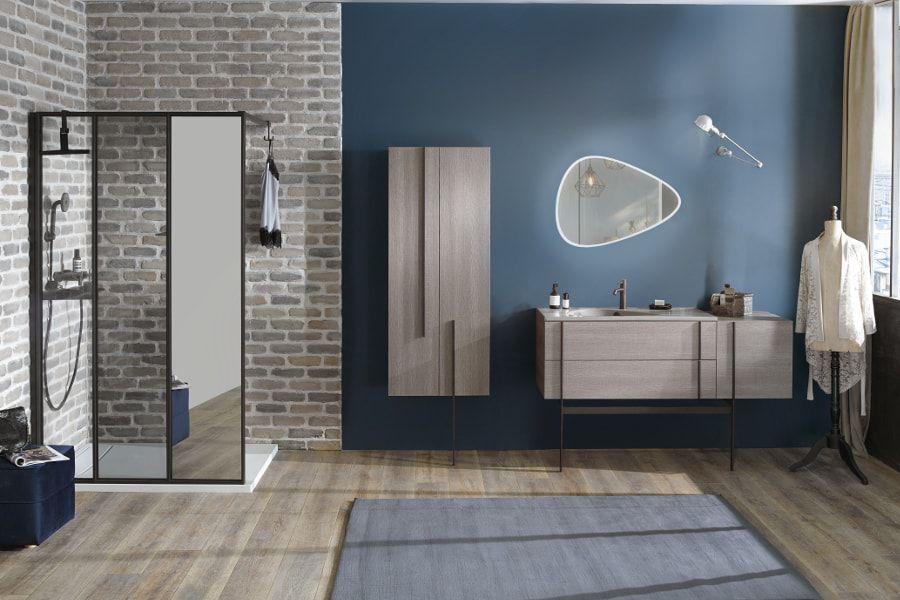 Une salle de bains parisienne avec des murs bleus et de la pierre ainsi qu'un espace douche ouverte