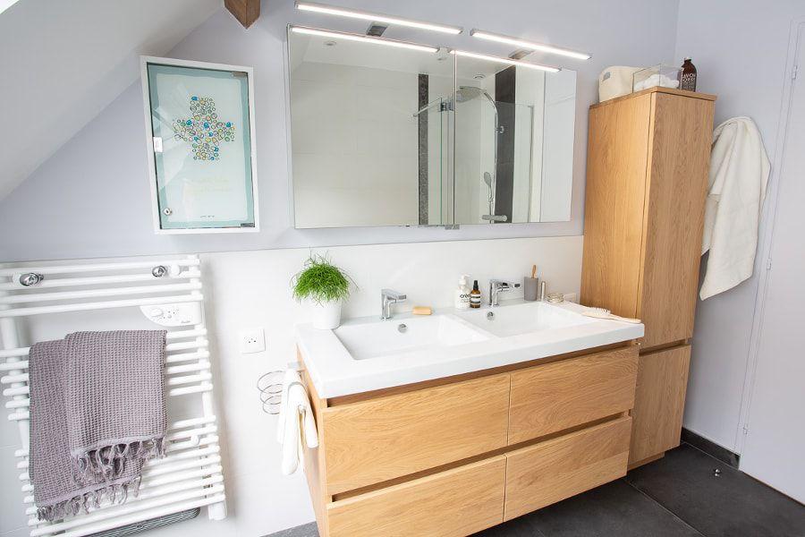 Une salle de bains aux couleurs anthracites, blanches et contenant un meuble vasque en bois clair avec des plantes vertes pour la décoration