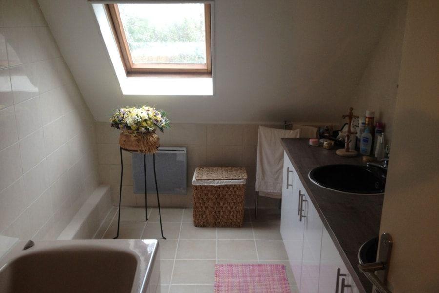 Une petite salle de bains familiale sombre sous les toits