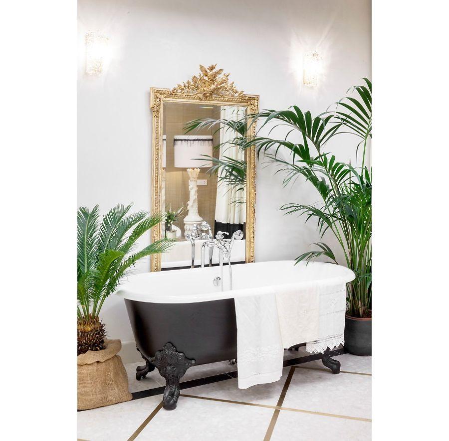 Des plantes vertes exotiques sur les côtés d'une baignoire noire dans une salle de bains