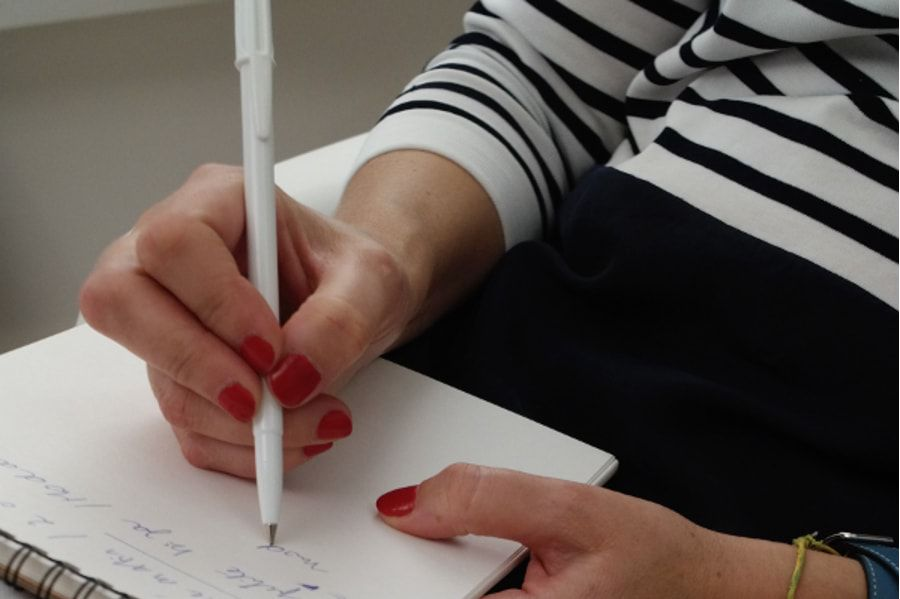 Une femme qui écrit dans un carnet de notes pour évaluer le temps des travaux de sa salle de bains