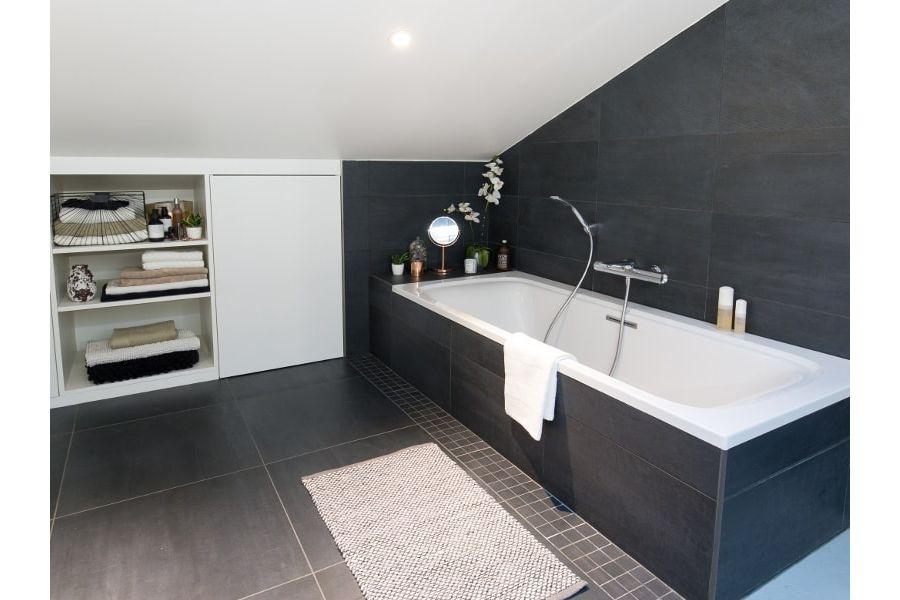 Une élégante baignoire dans une salle de bains aménagée sous des combles