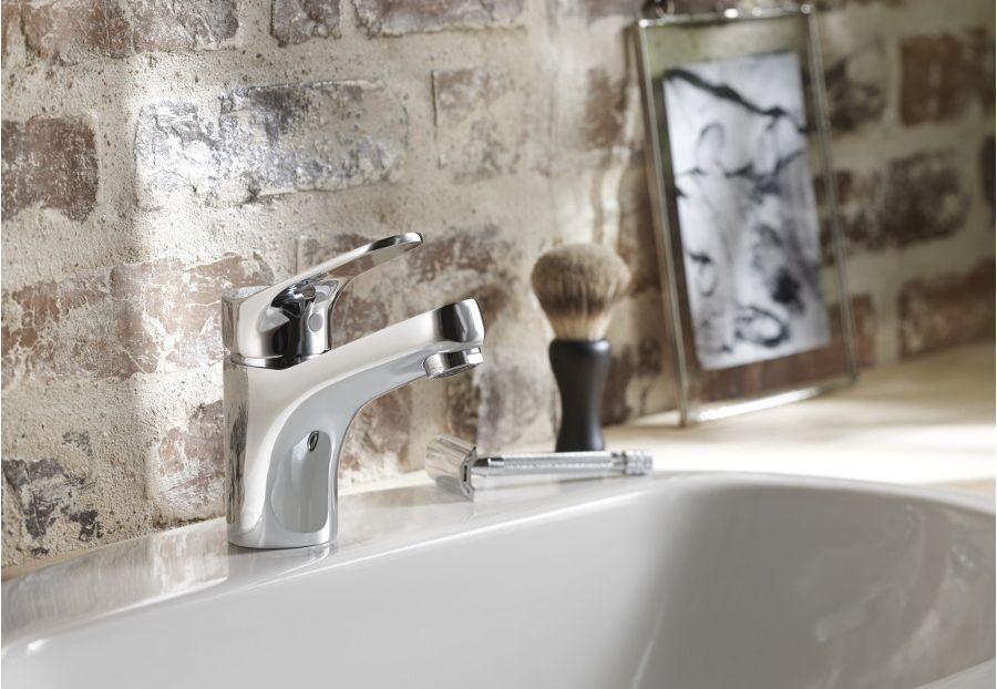 Un robinet chromé, un cadre photo et mur en pierre à l'esprit authentique et loft industriel