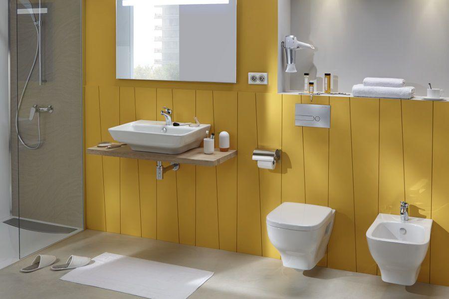 Une salle de bains jaune avec des murs en bois jaunes, un plan vasque et des WC