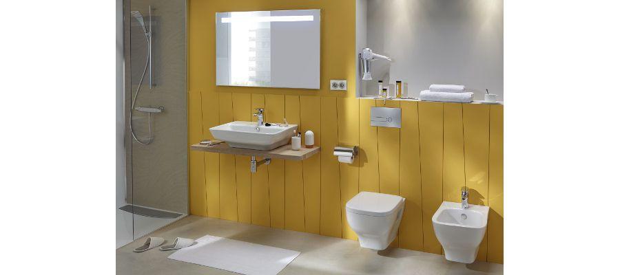 Une salle de bains avec des murs en bois jaunes, un plan vasque et des WC