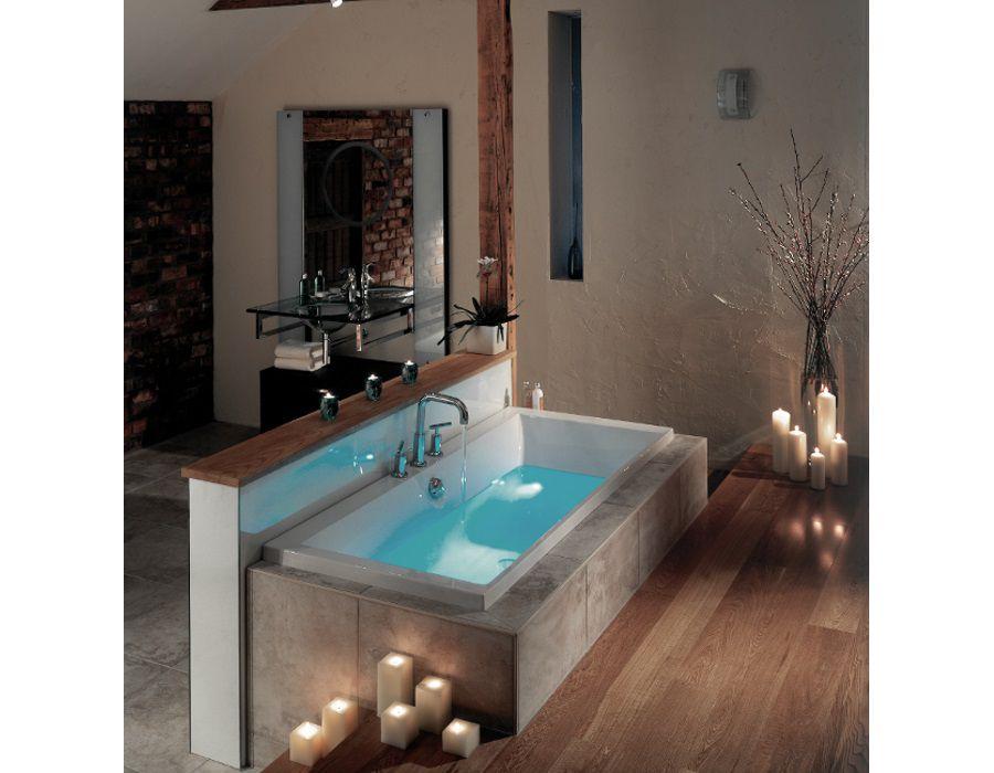 Des bougies de décoration disposées près d'une baignoire dans la salle de bains