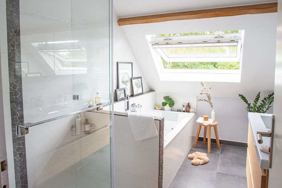 Une salle de bains lumineuse rénovée avec une baignoire, une douche et une double vasque avec meuble sous plan-vasque en bois