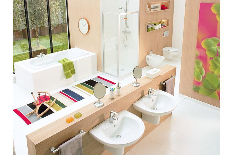 Des couleurs vives dans une salle de bains ODELA avec du carrelage blanc et des accessoires de couleurs