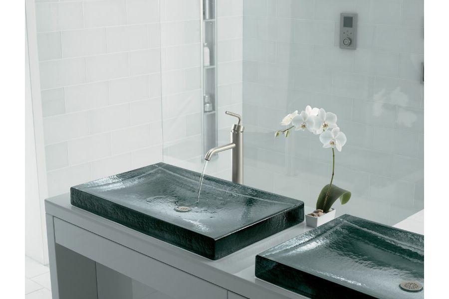 Une décoration minimaliste et raffinée avec un petit pot d'orchidées entre 2 vasques en verre