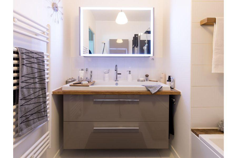 Une salle de bains avec des éclairages artificiels comme le miroir à éclairage périphérique LED et de l'éclairage au plafond