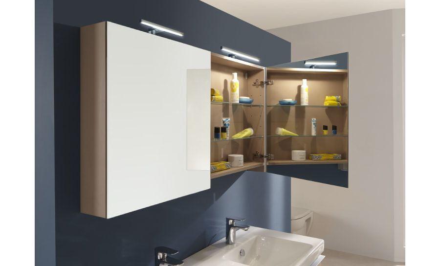 Un grand miroir au-dessus du plan-vasque dans une salle de bains bleue sans fenêtre