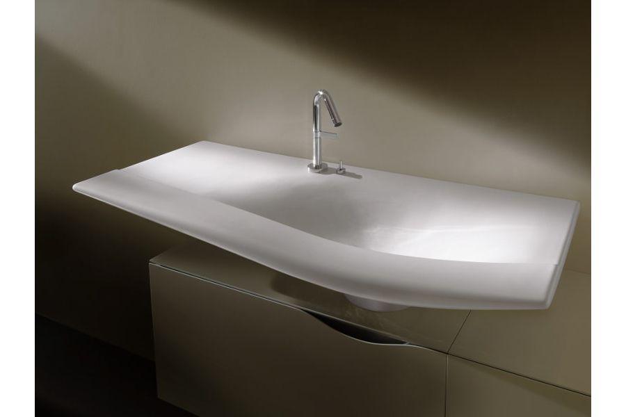 Une vasque blanche légèrement illuminée par un conduit provenant du toit