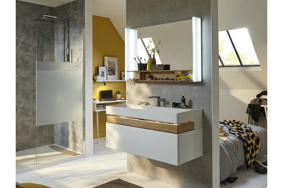 Des combles aménagés pour une espace de bain un meuble sous plan-vasque et un miroir derrière une cloison ouverte
