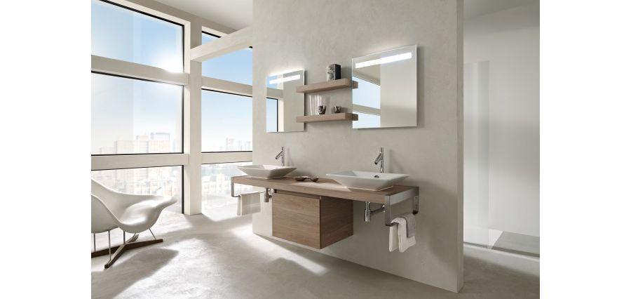 Une double vasque dans une grande salle de bains avec des miroirs et un meuble sous plan-vasque