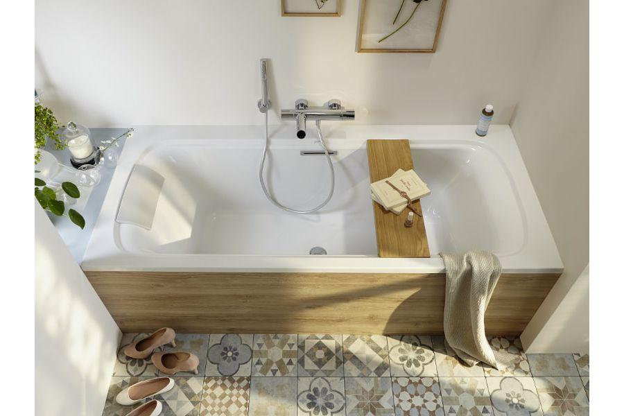 Un tablier de baignoire en bois avec avec des murs peints en blanc et un sol avec des motifs colorés