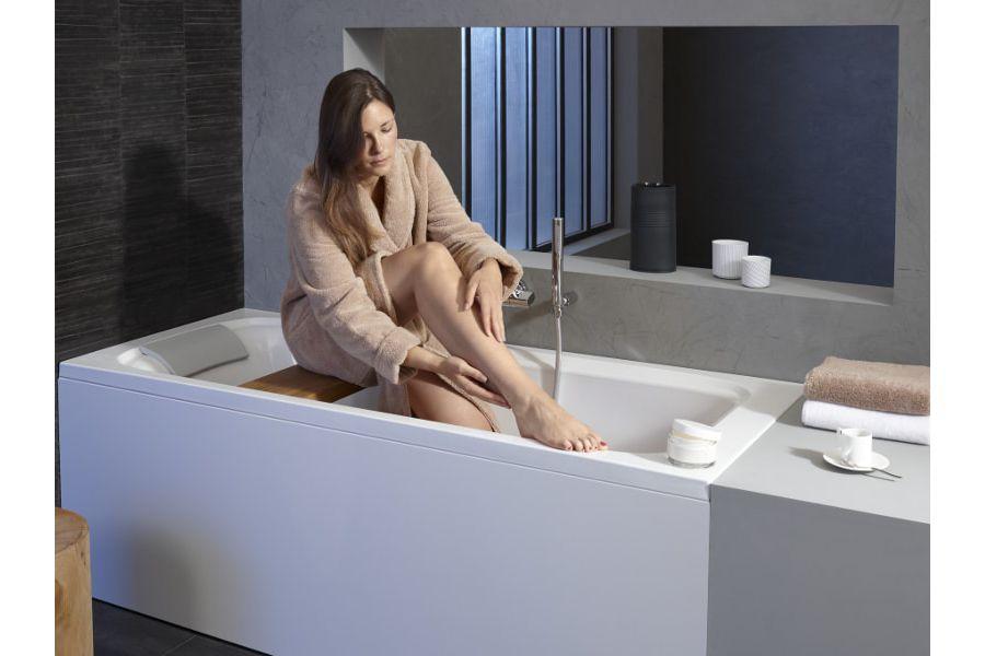 Une femme assise devant un tablier de baignoire gris qui rappelle la couleur du mur gris dans une salle de bains