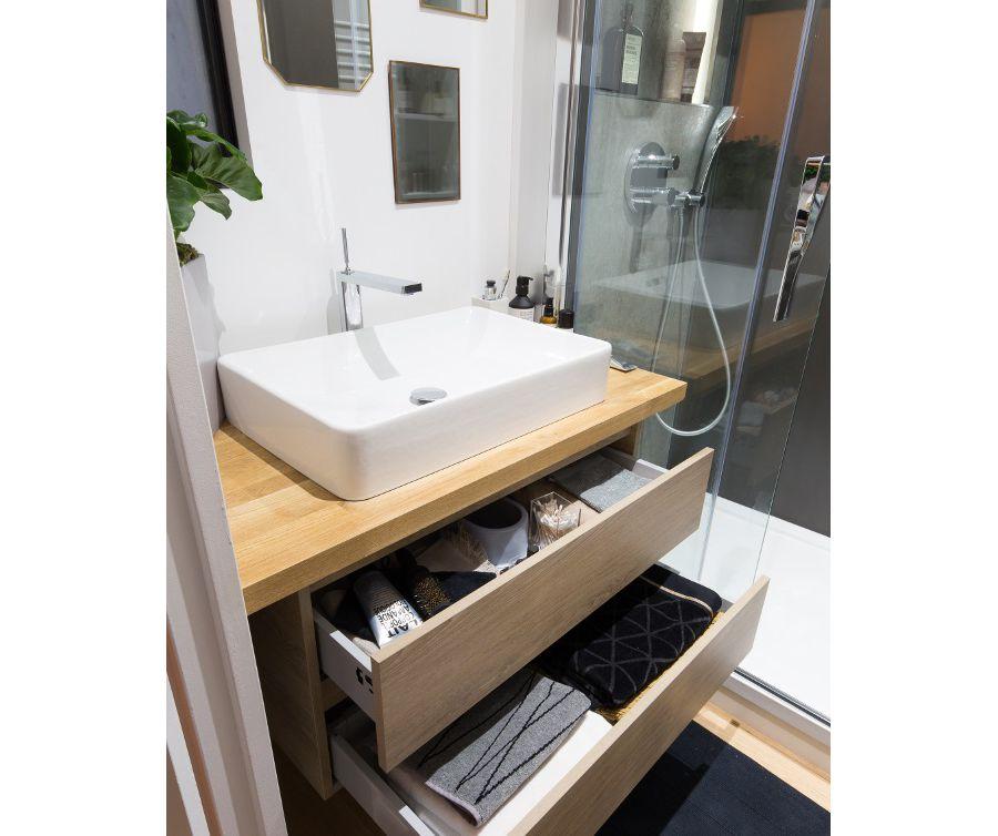Une salle de bains avec une douche et une vasque blanche sur un plan-vasque en bois