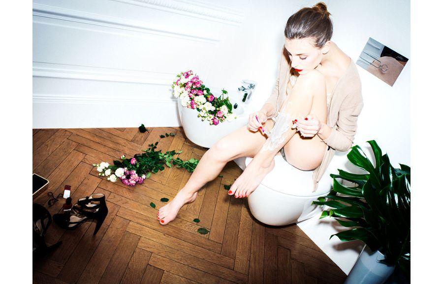 Une femme assise sur des WC et un bidet rempli de fleurs