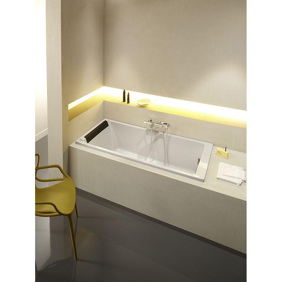 Une baignoire derrière une cloison ouverte ajourée