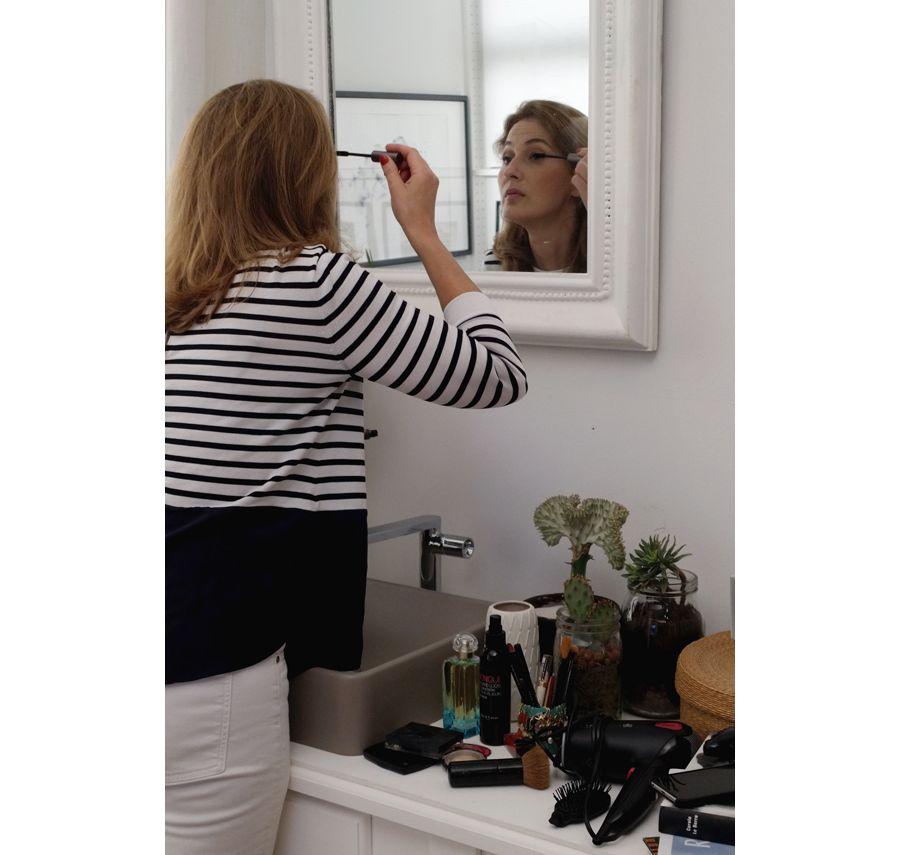 L'élégance d'une femme qui se maquille dans un miroir
