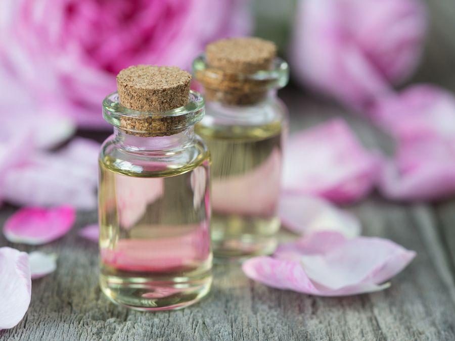 Des fioles d'huiles essentielles et des pétales de roses pour parfumer la salle de bains