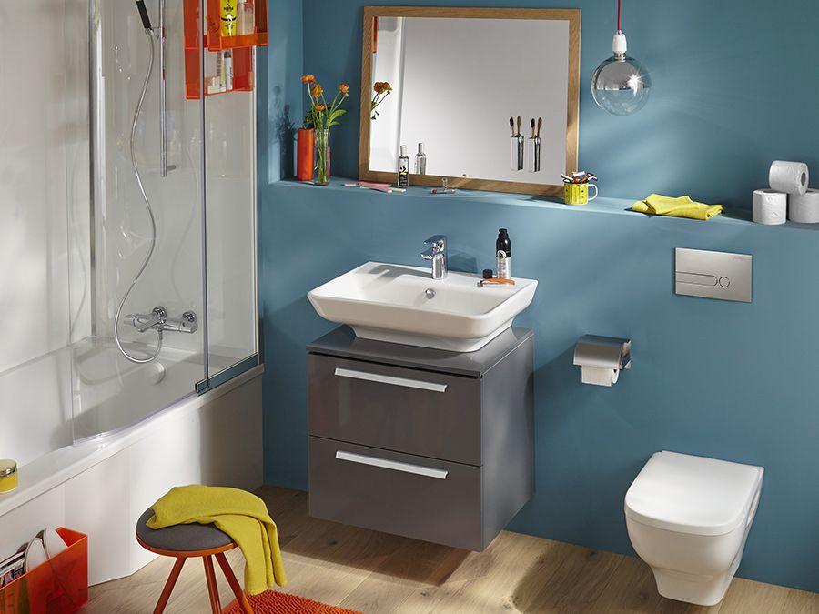Une vasque à poser, une baignoire et un WC dans une salle de bains bleue